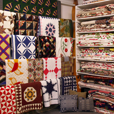 Image of the interior of Rocky Mountain Quilts, showing quilts hanging on racks in the left third of the picture, and quilts neatly folded on shelves in the right two thirds of the picture.