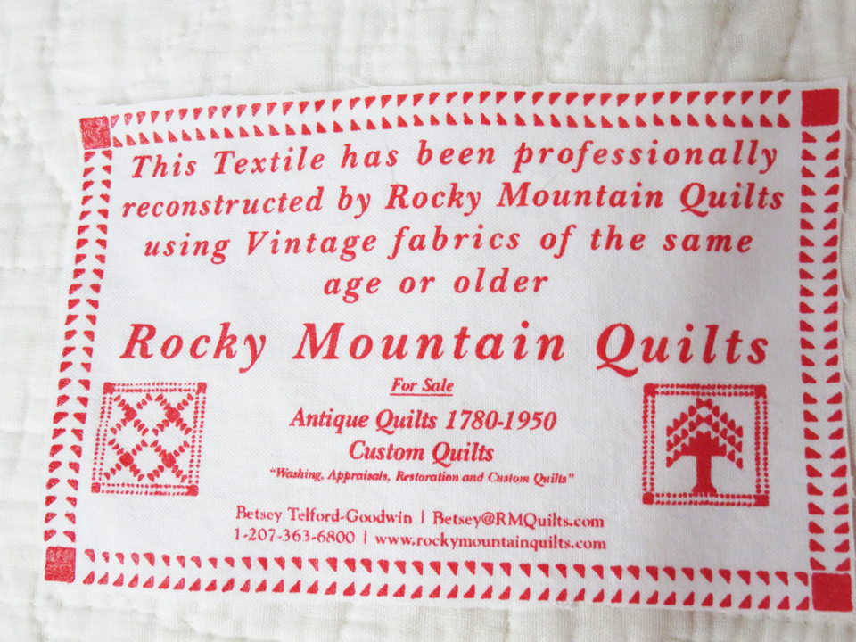 Image of the Rocky Mountain Quilts Label. Reads: This textile has been professionally restored by Rocky Mountain Quilts using Vintage fabrics of the same age or older. Rocky Mountain Quilts Antique Quilts 1780 - 1940 Betsey Telford 130 York St York Village, ME 03909 1-800-762-5914 www.rockymountainquilts.com
